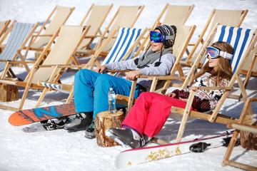Boy and girl sitting in sun lounger on ski terrain