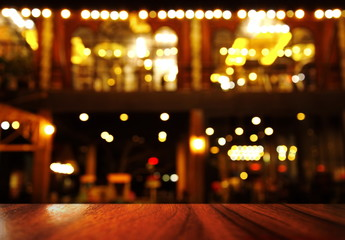 top of wood table with lamp light of bar or night club party background