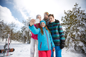Girl with family taking photo with cell phone
