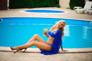 fashion outdoor photo of beautiful sensual woman wearing elegant bikini, posing beside swimming pool with cocktail