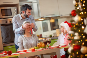 .Christmas dinner- happy father and children surprises mother.