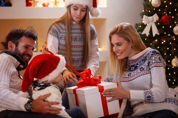 family enjoying sharing Christmas presents at home.
