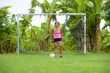 young happy and excited Asian woman in sport clothes playing football having fun at jungle soccer field with palm trees and grass