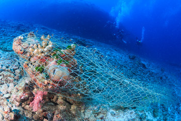 An abandoned fishing net (Ghost net) stuck on a tropical coral reef