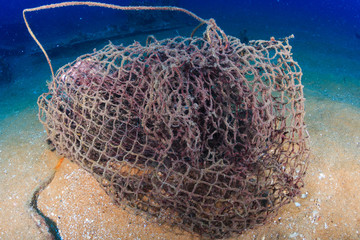 An abandoned fishing net (ghost net) on the sea floor