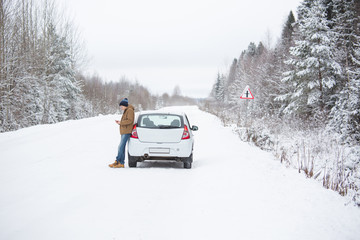Young man is standing near the car on a winter road. Cold weather, snow-covered trees in the winter forest. Man looks at mobile phone in his hands. Winter holidays.
