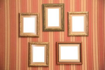 Several beautiful frames for photos of gold on a striped red wall