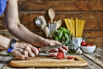 A woman cuts a cherry tomato and prepares a traditional Italian pasta