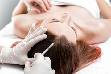 Needle mesotherapy. Cosmetic been injected in woman's head.