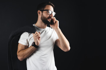 Trendy businessman with clear glasses and coat in shoulder wearing blank t-shirt and talking about something on smartphone
