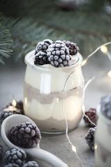 winter milk dessert with frozen blackberry