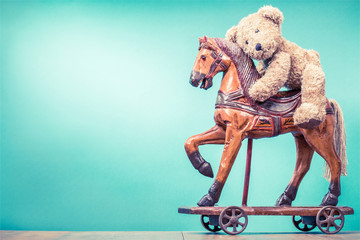Teddy Bear sitting on vintage antique Christmas wooden horse toy on wheels front mint green wall background. Holiday greeting card concept. Retro style filtered photo