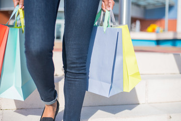 Woman walking out from a shopping mall with colorful shopping bags