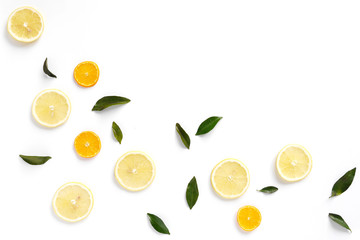 Pattern of fresh fruits on a white background, top view, flat lay. Composition of green leaves and slices of citrus fruits: lemon, mandarin. Healthy food background, wallpaper, collage.