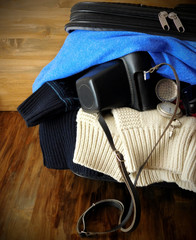 A stuffed suitcase with clothes and an old camera is ready for a trip. Travel concept