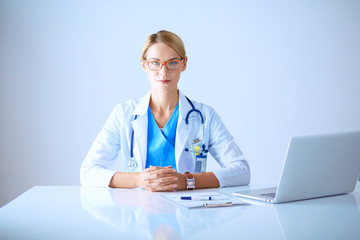 Beautiful young smiling female doctor sitting at the desk