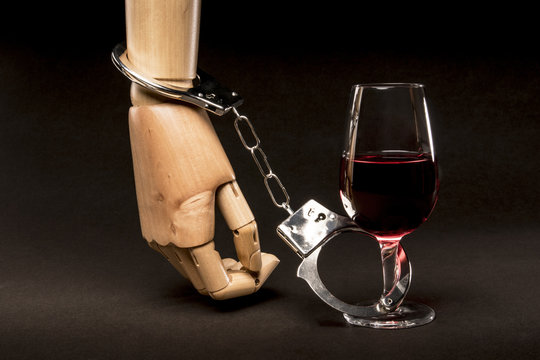 Hand tied to a glass of alcohol with handcuffs. Metaphor of addiction to alcohol. Isolated on dark background.