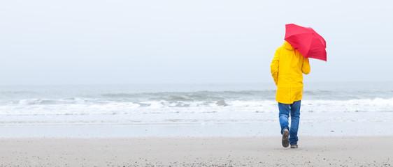 Mann mit gelbem Regenmantel und rotem Schirm am Strand