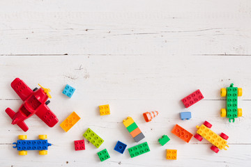 Top view on multi-color toy bricks on white wooden background. Children toys on the table.