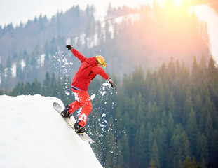Young man snowboarder jumping from the top of the snowy hill with snowboard in the evening at sunset at winter ski resort. Ski season and winter sports concept