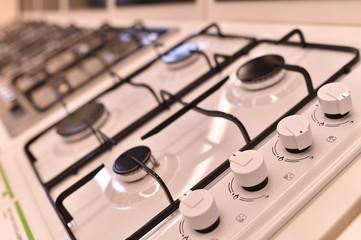 Газовые плиты, духовки, белого и серого цвета, четыре конфорки, с регуляторами.