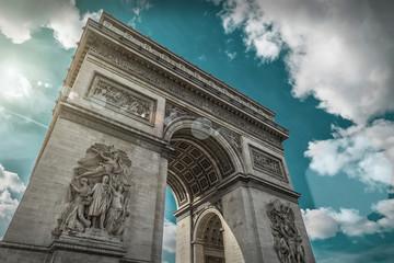 Arc de Triomphe in Paris under sky with clouds. One of symbols o