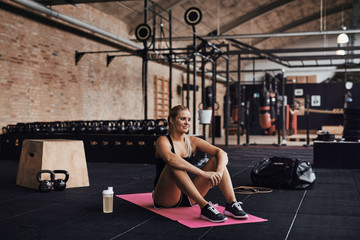 Smiling young woman sitting in a gym after working out