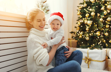 family mother and baby son at Christmas morning at tree