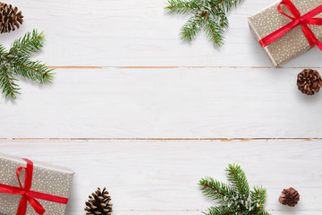 Christmas background with branches of fir, pinecones and gift boxes on white wooden board.