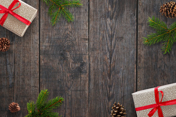 Christmas background with gifts, fir branches and pinecones over black wooden table. Top view.