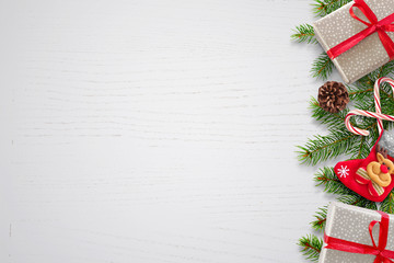 Christmas background with fir branches, gifts, sock and pinecones on right side. Free space for text on left side. White wooden background. Top view.