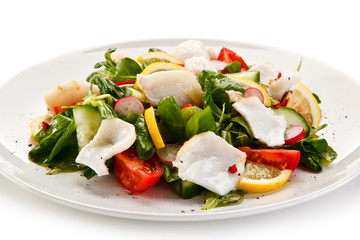 Salad with grilled fish fillet on white background