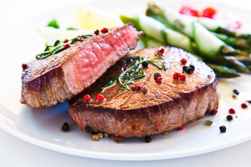 Grilled beefsteak with asparagus on white background