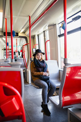 Young happy woman in city bus