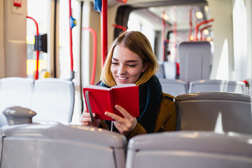 Young happy woman sitting in city bus and reading book