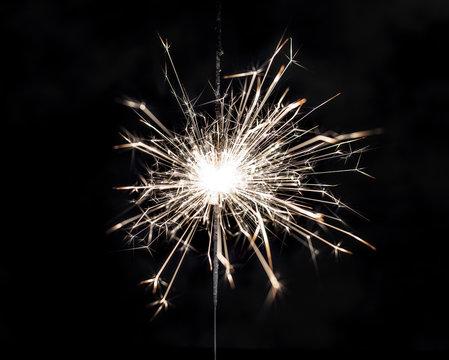 Burning sparkler on black background.