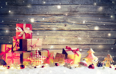 Rustic Gift Boxes On Snow With Christmas Ornament And Wooden Background