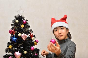 クリスマスツリーに飾り付けをする女の子