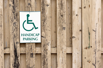 Handicap parking sign on a brown wood slat fence; off center with copy space for text