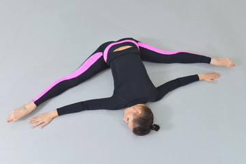 Beautiful woman in sportswear exercising at fitness studio, performing twine lying on the floor. High angle view.