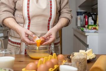 Oma zerschlägt ein Ei. Das Eigelb fließt in eine Glasschale. Sie backt Weihnachtskekse für ihre Enkel