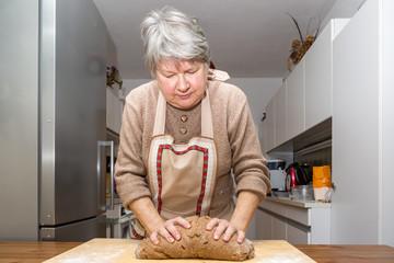 Oma knetet und formt den Teig für die Kekse auf einem Holzbrett