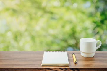 Hot coffee, , notebook and pen in nature background