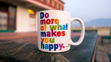 weiße Tasse mit einem Spruch zu Happiness