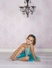 Adorable toddler girl wearing blue tutu in dance studio with vintage chandelier
