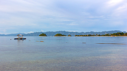 Fototapete - Tropical paradise in the lagoon of Coron Island, Philippines. Floating gazebo with a view on mountains backdrop on horizon.
