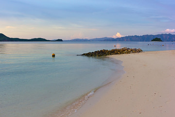 Fototapete - Tropical island paradise, Coron Island, Palawan Province, Philippines. Tranquil lagoon landscape with sandy beach and mountains backdrop on horizon at sunrise.