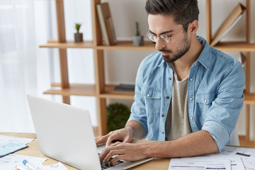 Serious male trader with trendy hairstyle, thick beard, wears casual outfit, prepares financial report about company`s income, keyboards at laptop computer, sits over modern office interior.