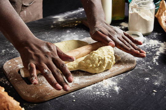 Cropped shot of man`s hands sheets dough with rolling pin indoor bakes delicious cakes or pastry, prepares for showing his cooking talents to audience or on television. People and baking concept