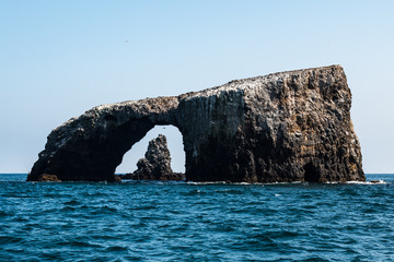 Arch Rock natural bridge with a volcanic rock formation in the background at East Anacapa Island in Channel Islands National Park off the coast from Ventura, California.